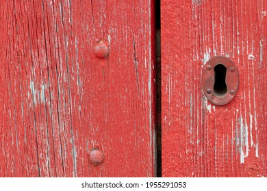 A closeup of a bright red vintage metal keyholder in a textured red wooden door. The exterior of the old woodshed has worn and wear patterns with some scuff marks.  - Shutterstock ID 1955291053