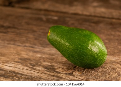 Closeup of bright ripe whole avocado with shiny peel composed on wooden table