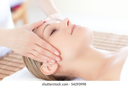 Close-up of a bright woman receiving a head massage in a Spa center
