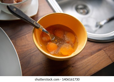 Close-up of bright yellow egg yolks in a yellow bowl with pepper and salt on kitchen table with natural light