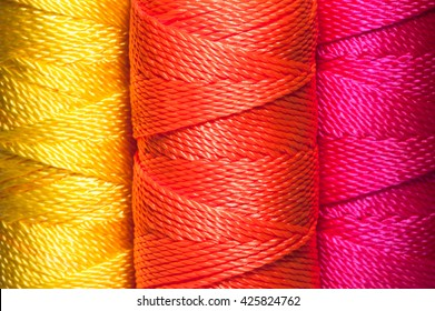 Closeup of Brightly colored nylon cord on a spool - Yellow, Orange, Pink