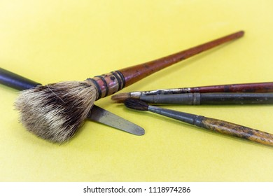 Close-up of bristles on an old artists paint brush. Yellow background