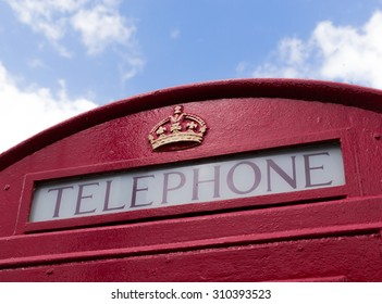 Closeup of a british red telephone box or booth against a blue summer sky