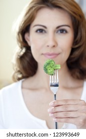 Close-up of broccoli on fork with woman in out of focus background