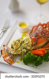 Closeup of a broiled or baked lobster tail with vegetables.