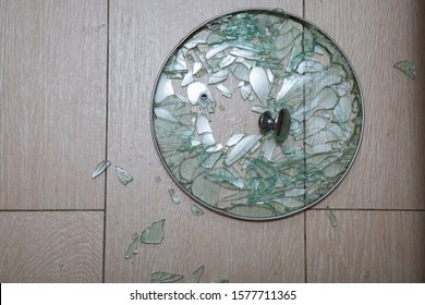 A close-up of a broken glass lid lies on a stake of tile. shards of glass shine. soft focus, top view