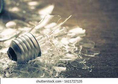 Closeup broken light bulb on the ground, bad idea metaphor or fail concept