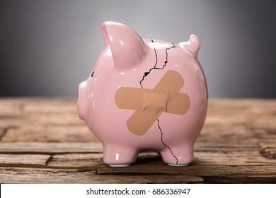 Closeup of broken pink piggybank with bandage on wood