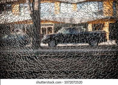 Closeup of broken window of tempered glass. Street view on the other side.