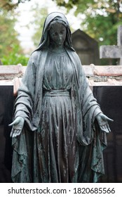 Closeup of bronze statue of the virgin mary  on tomb in a cemetery