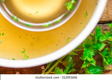 Closeup of broth in a saucepan and ladle and parsley
