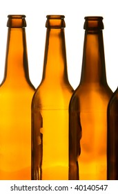 Closeup of brown beer bottles. Backlit, studio shot. Isolated on white.