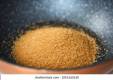 Closeup of brown demerara sugar in a wok