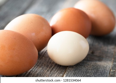 Close-up of brown eggs and one small lighter egg on wooden table.