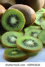 Closeup of brown kiwi fruit with green kiwi slices.