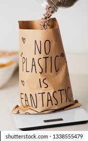 closeup of a brown paper bag on an electronic scale, being filled with dry lentils, with the text no plastic is fantastic written in it, on a white stone countertop