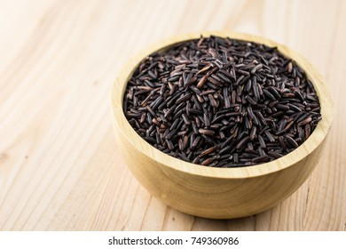 Close-up brown rice or riceberry organic food in bowl healthy on wood texture