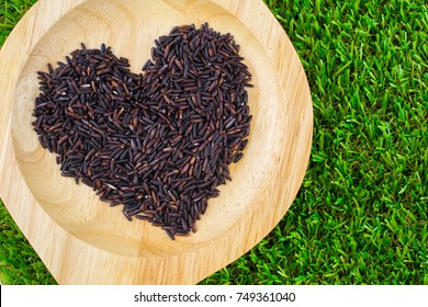 Close-up brown rice or riceberry organic food in bowl healthy on wood texture and green grass