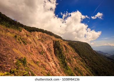closeup brown stony mountain slope with tropical forest on top against white clouds in blue sky