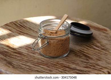 Closeup of brown sugar in sugar bowl on wooden table.