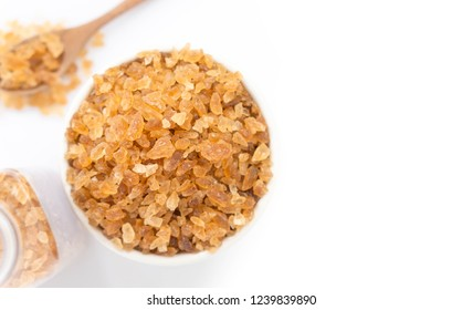 Closeup brown sugar on ceramic bowl isolated with white background, top view