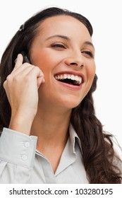 Close-up of a brunette beaming while calling against white background