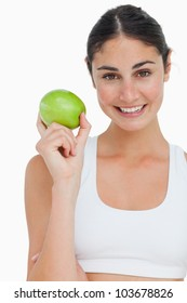 Close-up a brunette holding an green apple against white background