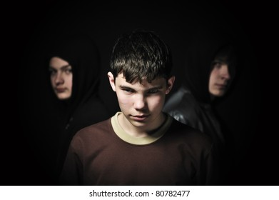 Closeup of a brunette teenager with his friends barely visible in the background