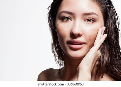 Closeup of a brunette woman making a face peeling scrub on a white background isolated