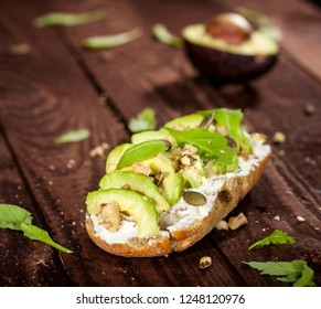 Closeup of bruschetta with avocado, mascarpone, rucola and nuts on a wooden table.