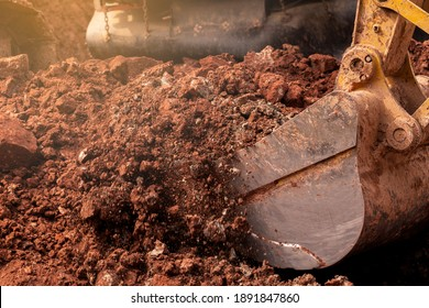 Closeup bucket of backhoe digging the soil at construction site. Crawler excavator digging on demolition site. Excavating machine. Earth moving equipment. Excavation vehicle. Construction business.