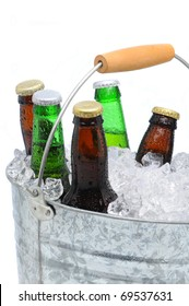 Closeup of a bucket  filled with ice cubes and an assorted beer bottles on a white background.