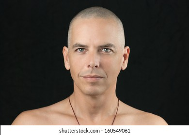 Close-up of a buddhist man looking to camera, shaved head and shirtless.
