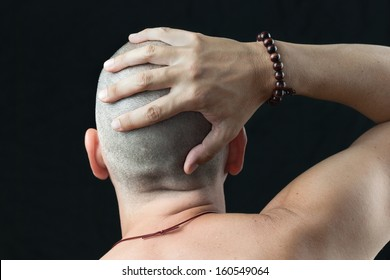 Close-up of a buddhist man wearing a mala feeling his newly shaved head, shirtless and shot from behind.