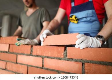 Nahaufnahme von Bausteinen mit professionellem Aufbau. Arbeiter bei der Arbeit, Mauern aus Ziegelstein, Bauunternehmer und Arbeiter. Masken mit Beton- und Schutzhandschuhen