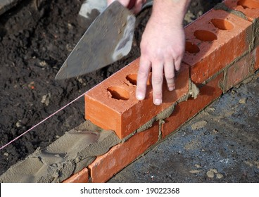 Close-up of builder laying bricks of new build