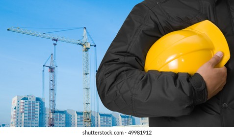 Closeup of builder with yellow helmet at building panorama