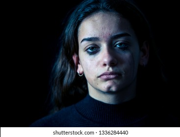 Closeup of a bullied, depressed, alone, tired, stressed young child girl crying. Isolated on black background. Human emotions, Childhood depression, emotional pain. Bullying and child abuse concept.