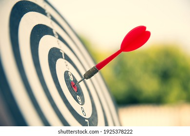 Close-up the bullseye or bulls eye target or dart board has dart arrow throw hitting the center of a shooting for business targeting and aim to winning goals concepts