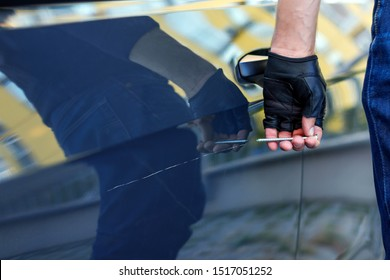 Closeup bully hands in black gloves are scratching automobile with nail, pin. Bandit is spoiling appearance of private car. Man is making scratch on auto without signaling. Vandalism act concept.