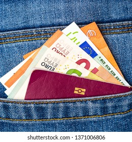 Closeup of a bunch of Euro banknotes and EU passport peeking out of blue jeans back pocket. Travel or shopping, emigration concept.