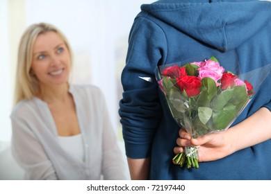 Closeup of bunch flowers hidden behind boy's back