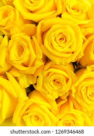 A close-up of a bunch of fresh roses with yellow petals in full bloom in a vertical image format.