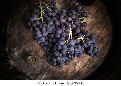 Close-up of bunch of ripe red grapes on a rustic wooden wine cask, top view