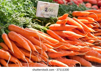 Closeup of bunches of carrots with a sign indicating their price, taken at a local outdoor farmers market.