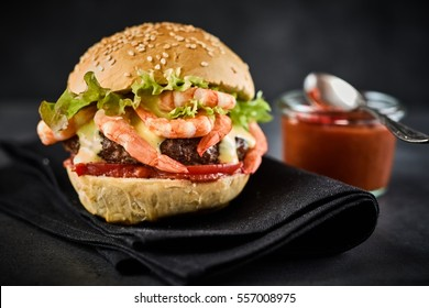 Close-up of burger with shrimps and meat served on folded black napkin and jar of red sauce