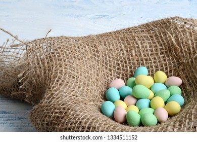 closeup burlap bird nest with easter candy eggs