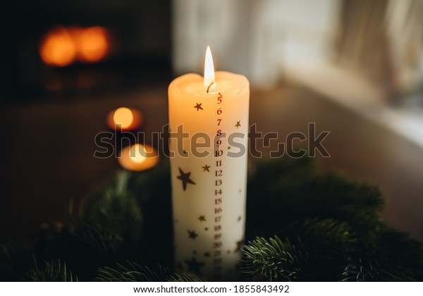 Close-up of a burning christmas candle in wreath. Christmas candle with december month date numbers.