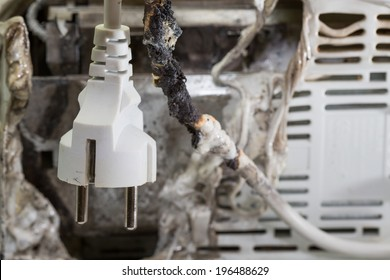 Closeup of burnt cable with burnt electrical appliance