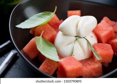 Closeup of burrata cheese and watermelon salad served in a black bowl, selective focus